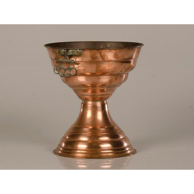 An unusual and tall copper vase with a double bowl shape from Edwardian England c.1910. The curious repetition of the...