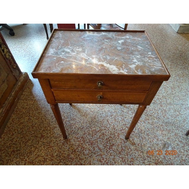 Very sweet French wood side table with a marble top ( white, grey and brown colors ) and two drawers. Round tapered legs....