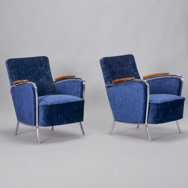 Pair of Bauhaus armchairs have a curvy polished steel frame, wood accented arm rests and have been recently upholstered in...