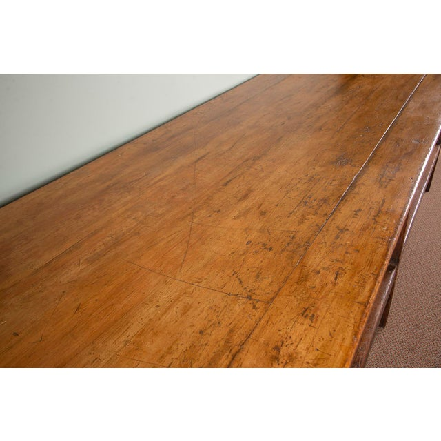19th century French drapers table is made of pine and retains its original finish. This over-sized working table was...