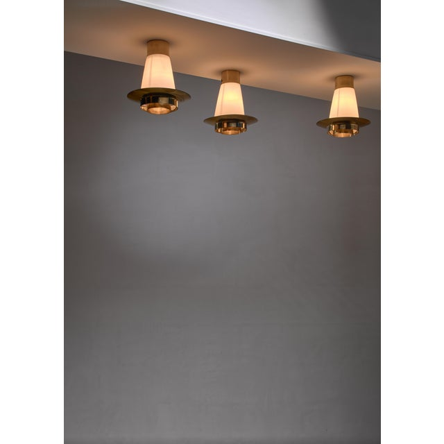 A set of three model 71-126 flush mount ceiling lamps by Yki Nummi for Orno. The lamps have a cone shaped opaline glass...