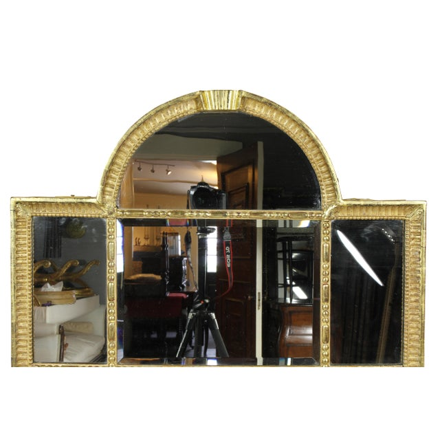 With an arched top with central keystone, individual beveled mirror plates combining to form a rectangle. The frame with...