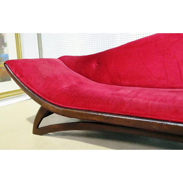 Adrian Pearsall gondola style sofa with a walnut frame and red upholstered fabric.