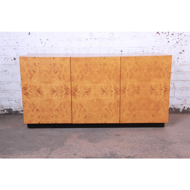 An exceptional mid-century modern burled olive wood credenza or sideboard designed by Milo Baughman. The credenza features...