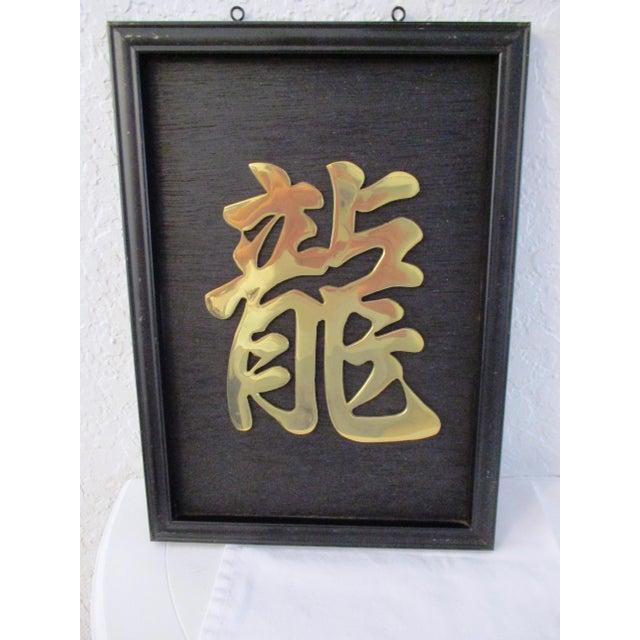 Cool vintage polished brass Chinese symbol mounted on painted black wood displayed in a black metal frame. Two metal rings...
