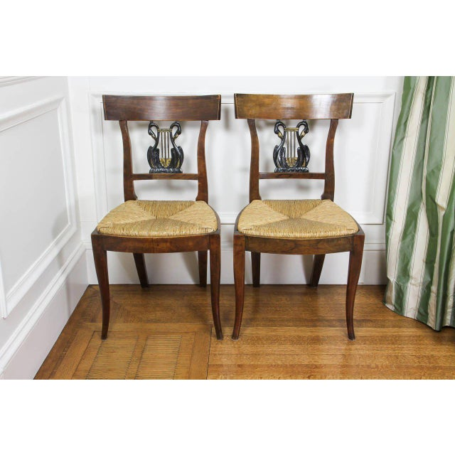 Each with tablet crest rail over a lyre form splat, rush seat raised on square tapered legs.