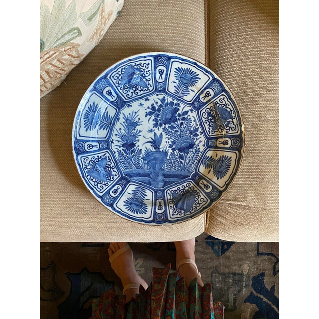 A rare delft charger circa 1670, featuring a botanical motif with a dragonfly pictured in the center. The marking on the...