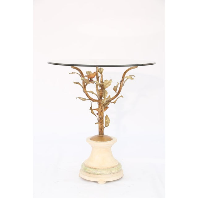 Side or end table having a round top of glass, on frame of gilded iron, its arms formed as leafy branches with birds...