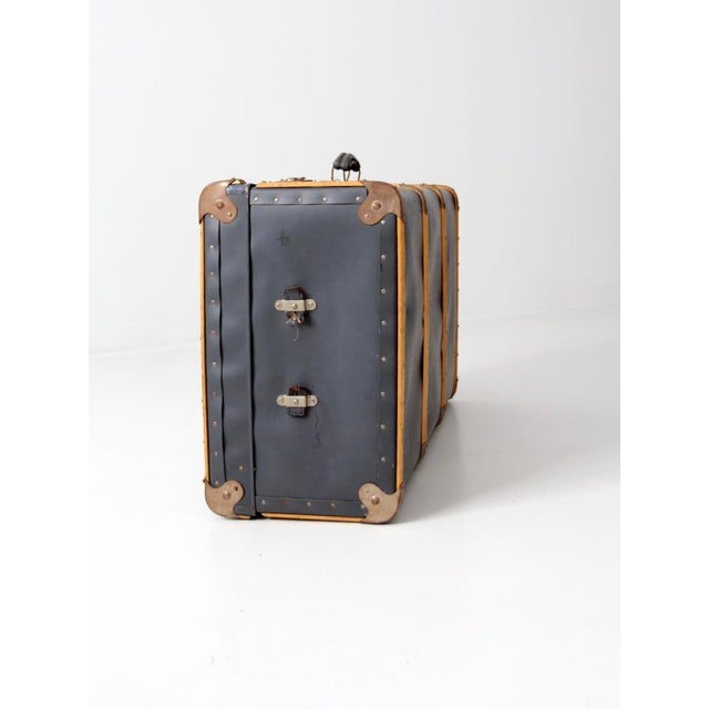 This is a large vintage suitcase with bentwood banding. The steamer style trunk features a blue hard case shell with...