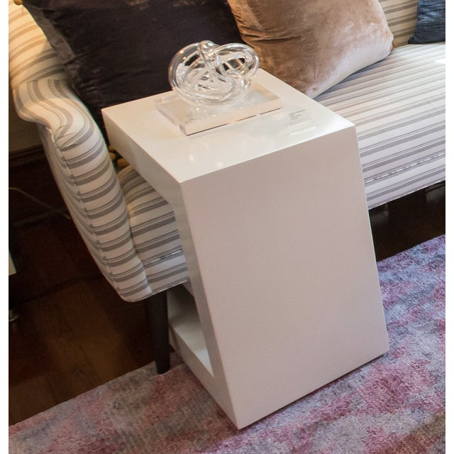 C shaped side table in white lacquer. Great for pulling the base under the sofa to place a laptop or drink on.