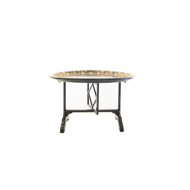 Black oval wood lacquered tray with gold foliate border decoration on a (later) stand painted with a gold filet on black....