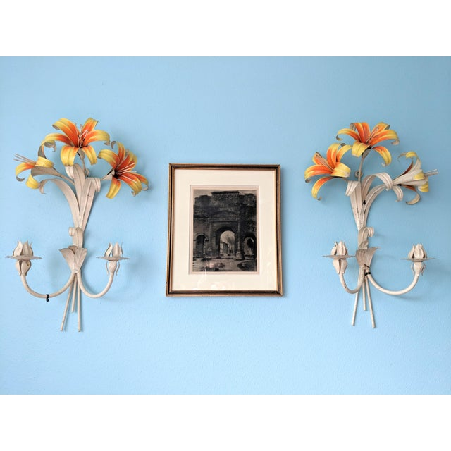 Stunning wall sconces perfect for holding candles or just hanging on their own. Lilies painted vibrant orange and yellow...