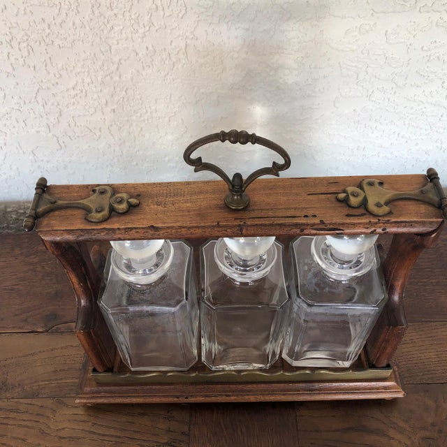 A very special three bottle crystal decanter tantalus executed with brass mounts on an oak platform. The latch mechanism...