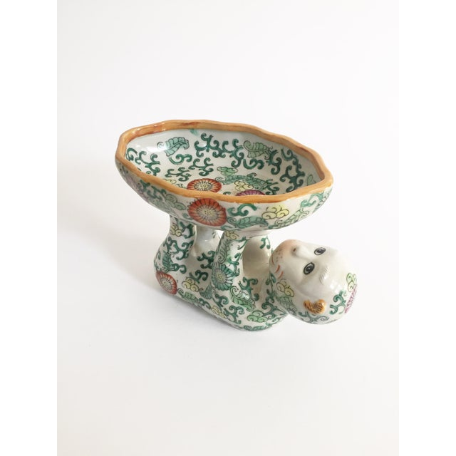 A wonderful chinoiserie ceramic dish in the shape of a monkey holding a dish. Beautiful painted detailing throughout....