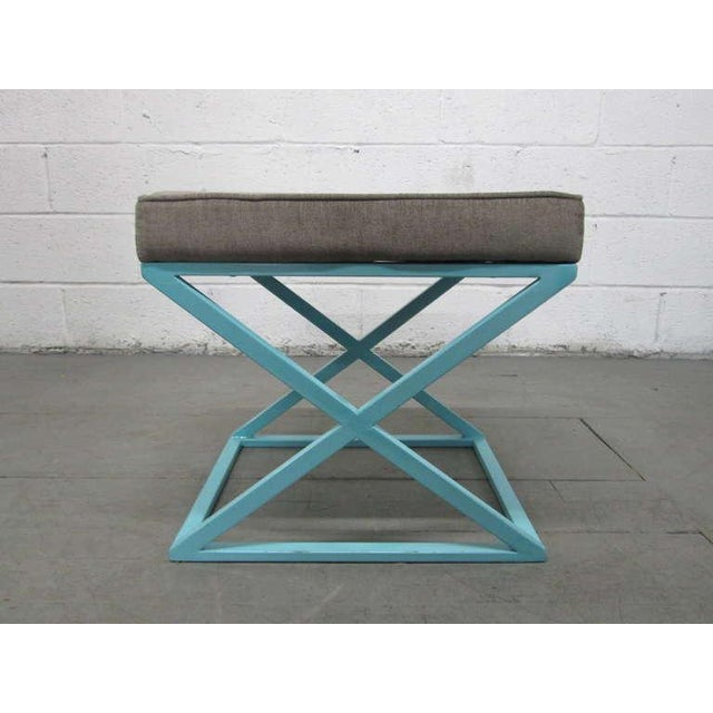 Pair of painted metal X-base benches with upholstered cushioned seats.