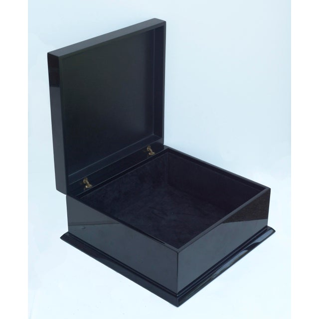A decorative black lacquer accessory box with red coral accent by Jacques Blanchard. Box features a black velvet lining....