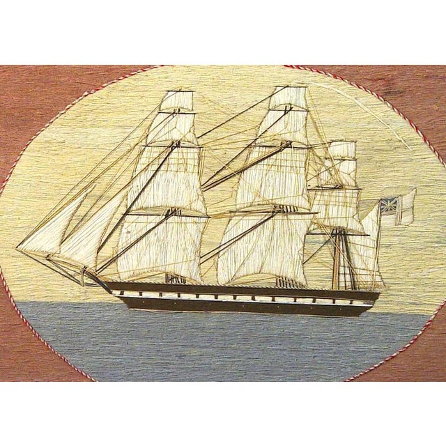 The sailor's woolwork, known as a woolie, wool is made in an unusual oval format. It is bordered by braided red and white...