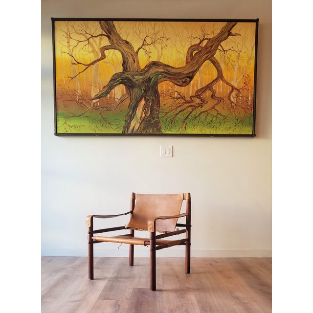 1960's Arne Norell Sirocco Chair in rosewood with natural tan leather and brass hardware accents.