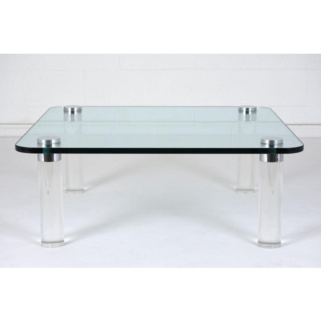 This 1960's Mid-Century Modern-style coffee table features a glass top and lucite legs. The thick glass top features a...
