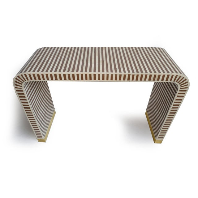 Stunning striped chocolate brown resin and bone console table. Modern simple waterfall design with brass sheet wrapped base.