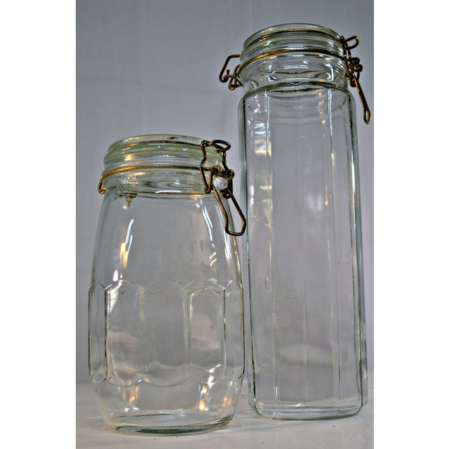 This is a pair of vintage, clear glass canisters feature wire bale clamp lids. The shorter jar has some chipping in nozzle...