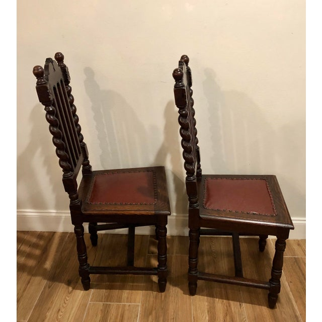 Lovely pair of wooden gothic barley twist chairs with red leather seats and antique nailhead trim