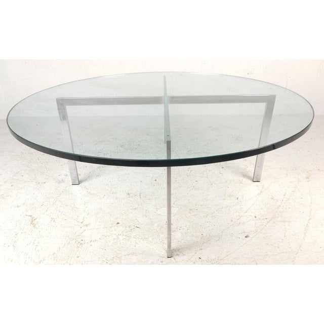 """This vintage modern circular coffee table features a heavy """"X"""" shaped base with 1"""" thick green glass. The unique design..."""