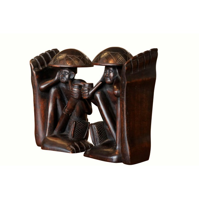 A pair of wooden book ends carved with traditional figures. A man and a woman hold smoking pipes and are sat with their...