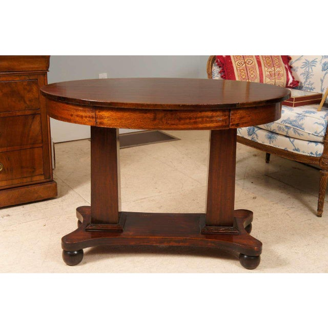 Pillar and scroll mahogany Empire table with single drawer.