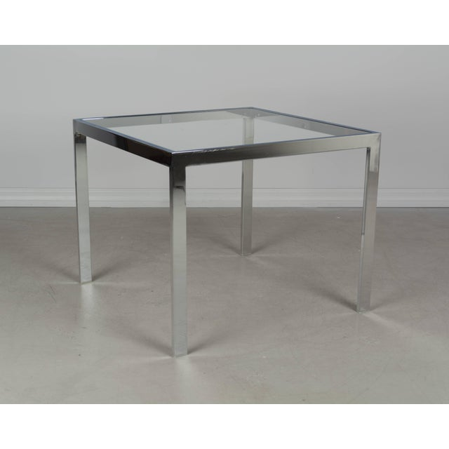 Milo Baughman chrome end table with inset glass top. Polished chrome finish is in excellent condition. Light scratches in...