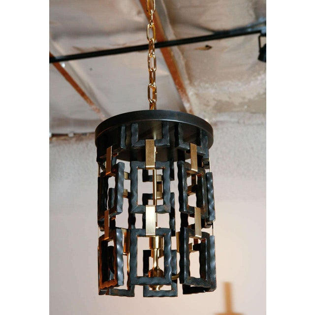 Paul Marra Link Fixture shown as pendant in brass and oil rubbed bronze finish, hung by brass chain and canopy. One...