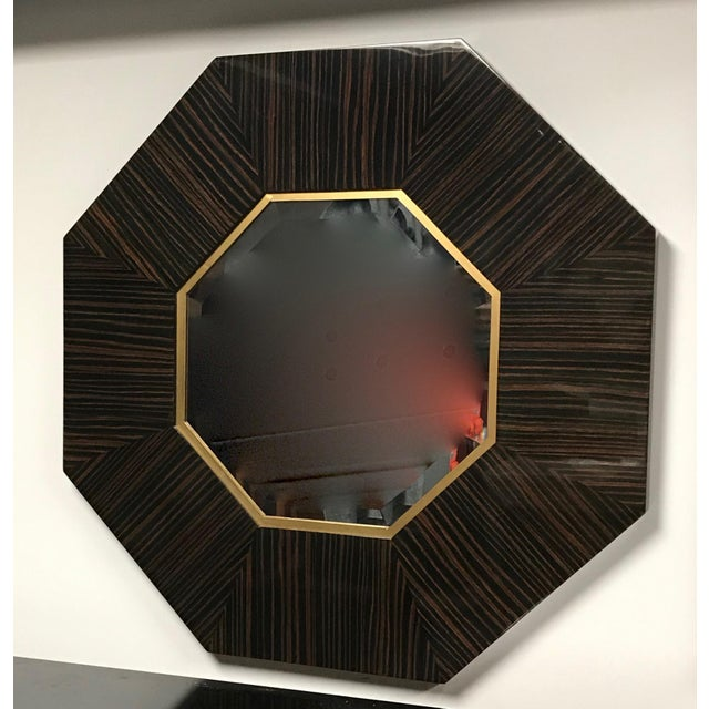 Stunning French Art Deco eight sided Macassar ebony hanging wall mirror. With beautiful beveled glass and gold accents.