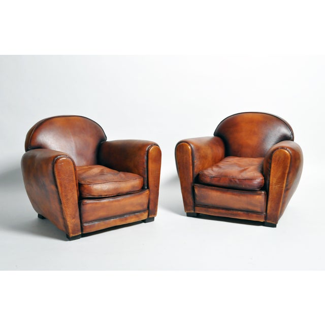 Handsome pair of brown armchairs from France made from leather and wood, circa 1960. Bulbous and comfortable the chairs...