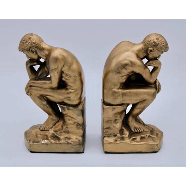 A stunning set of 1928 Thinking Man Bookends with a custom gold finish that exudes a brilliant luster with bronze...