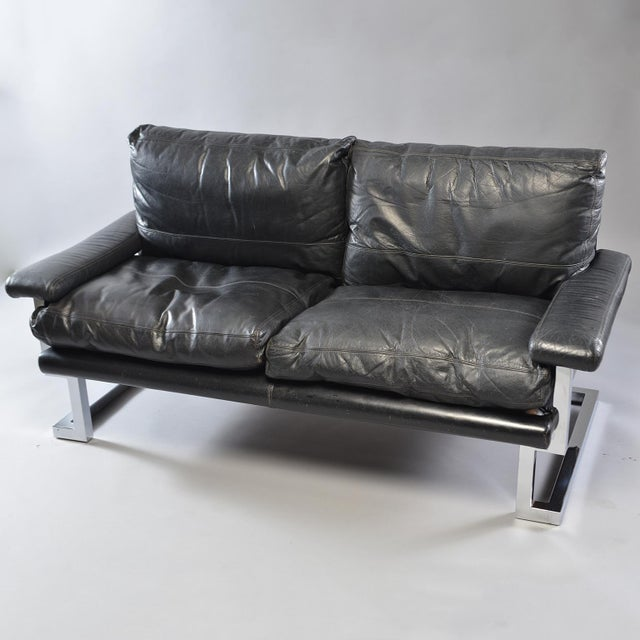 Circa 1970s pair of black leather and chrome sofas designed by Tim Bates for the Mandarin Collection of UK furniture maker...