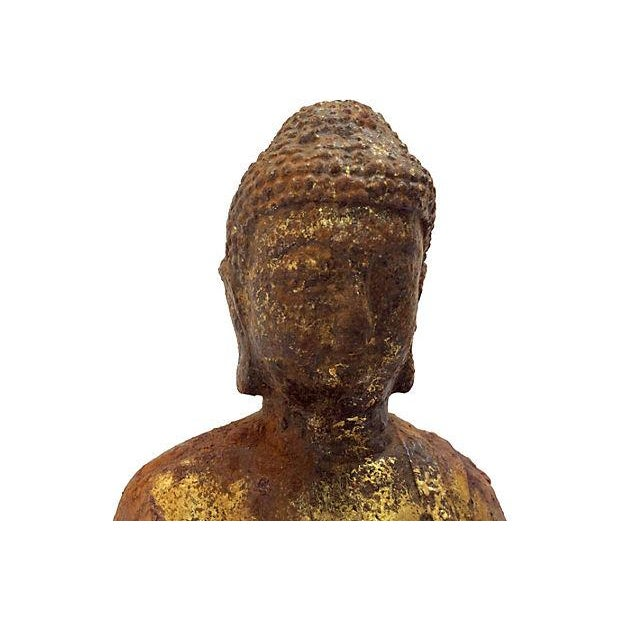 Antique cast metal seated Buddha weathered to perfection with remnants of gold gilt.