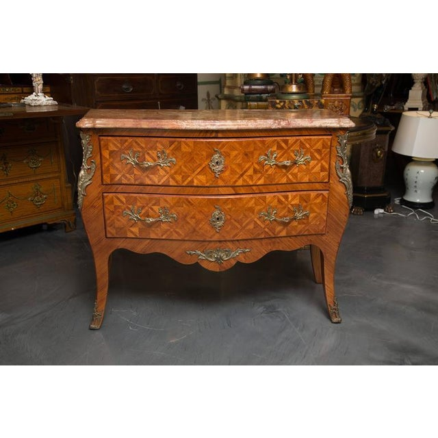 This is a lovely pair of Louis XV style kingwood inlaid commodes having rouge beveled marble tops over two long drawers...