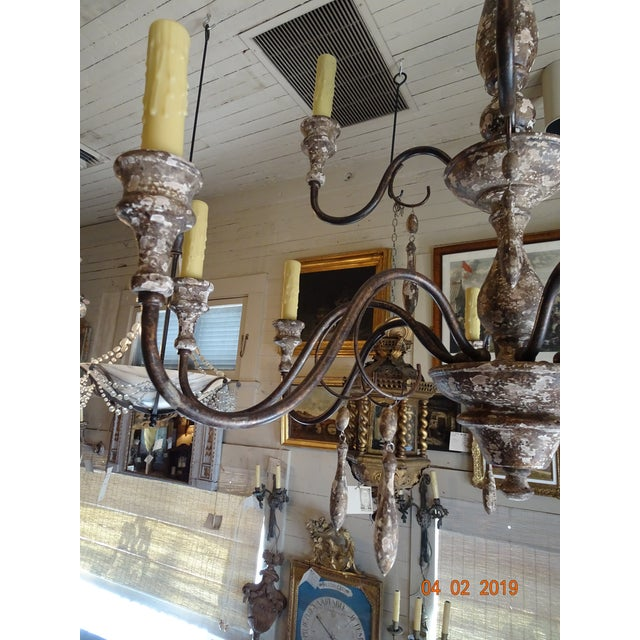 2 tiers wood stem chandelier ( 12 lights ) with iron scroll arms and wood tassels hanging from each scroll. This...