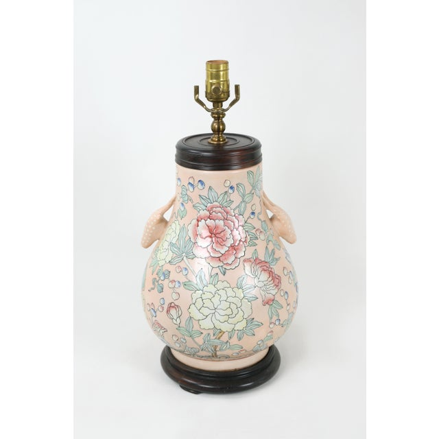 A famille rose vase lamp with animal head handles and blooms of flowers in various colors against a soft pink background.