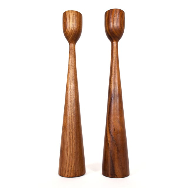 Pair of iconic Danish mid century teak candlesticks. Their tapered design displays beautifully with or without candles.