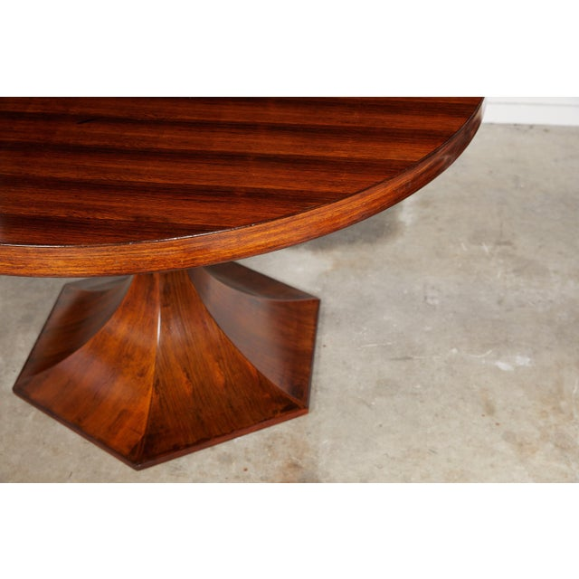 20th century Italian dining table of palisander wood with a round tabletop on a hexagonal tulip shaped pedestal base.