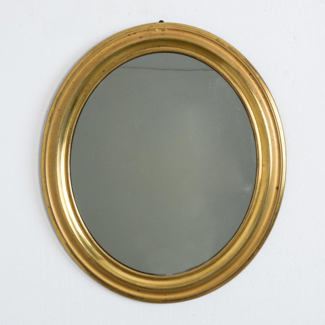 From France circa 1880. An oval brass mirror, in Napoleon III style. All original details, and a simple and dynamic form...