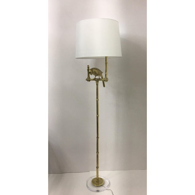 A pair of wonderful floor lamps with parrots perched on a stand. Solid brass with Lucite bases. Newly re-wired. No shades.