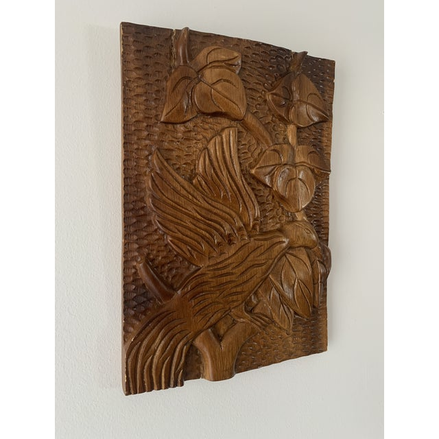 Made from one piece of wood, this hand carved plaque features an open winged bird on a branch surrounded by leaves....