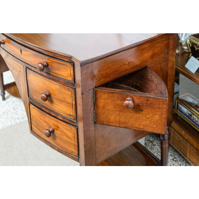 Unusual English, mahogany, bowfront sideboard with arched central opening. Drawers have original wood knobs and ebonized...