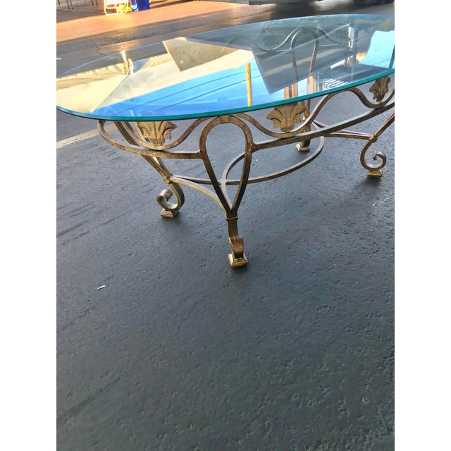 """Gold color heavy metal base with oval glass top. The base measures 42"""" x 26 .5"""" and 19"""" tall. The glass top is 3/8"""" thick..."""
