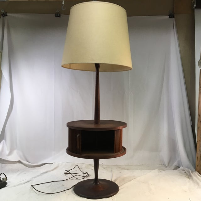 This unique and one-of-a-kind vintage lamp is sure to be a conversation piece. The base, attached table, and pole are all...