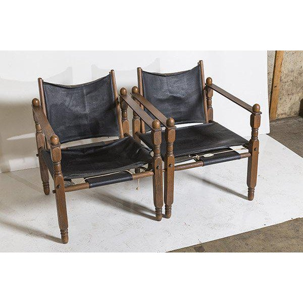 A fantastic pair of 1960s Danish modern safari chairs in the style of Arne Norell. Lucious oak frames with vinyl seats....