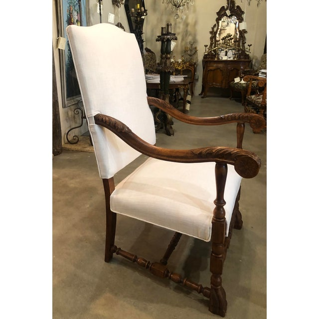 Antique French chair with carved arms and new linen blend off white upholstery.