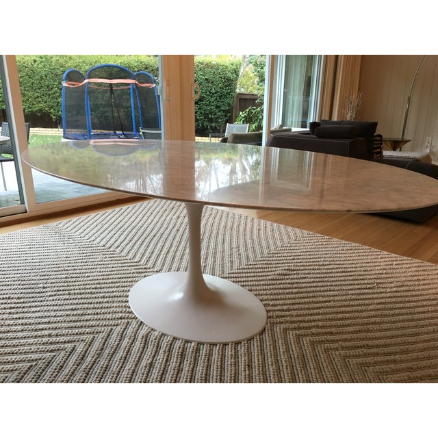 Simple and sophisticated oval-shaped tulip table with carrara marble top. This replica of Eero Saarinen's tulip pedestal...